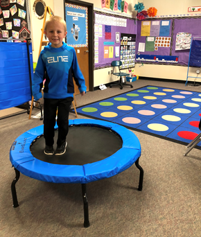 Kindergartener jumping on fitness trampoline to increase classroom activity