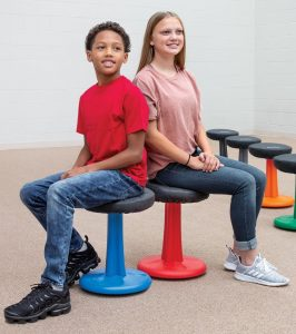two students sitting on active stools